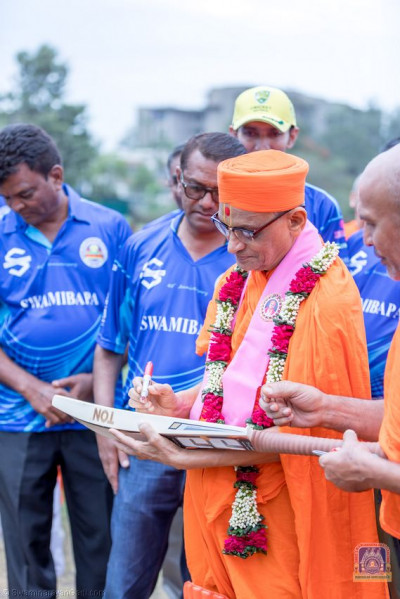 H.D.H Acharya Swamishree autographs the cricket bat