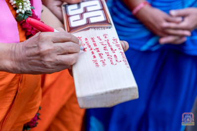 H.D.H Acharya Swamishree writes His Divine blessings on the cricket bat