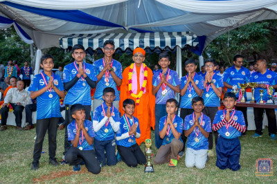 A group photo of H.D.H Acharya Swamishree with Swamibapa cricket team