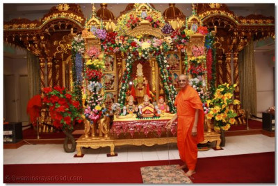 His Divine Holiness Acharya Swamishree gives darshan gently swinging Lord Swaminarayanbapa Swamibapa seated on the hindola