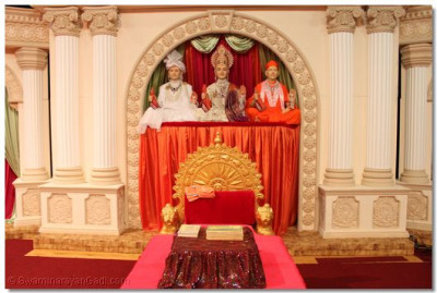 Lord Swaminarayanbapa Swamibapa seated on a beautiful stage backdrop that has been constructed and decorated by sants and disciples