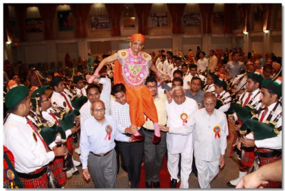 Disciples carry His Divine Holiness Acharya Swamishree onto the stage as Swamibapa Pipe Band perform