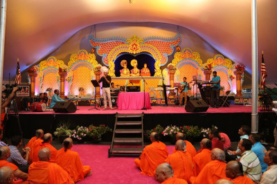 Jeffrey Iqbal rouses the audience as Lord Swaminarayanbapa Swamibapa watches above him