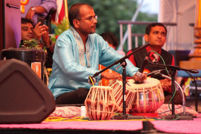 A band performer accompanies Jefrrey Iqbal with up-beat rhythms