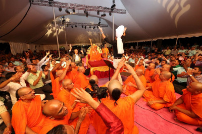 Jeffrey Iqbal rises to his feet as he is overcome by his emotions while singing to Acharya Swamishree