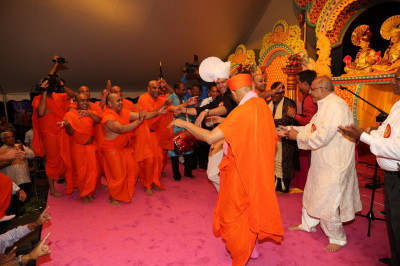Jeffrey Iqbal engages in a friendly dance with Acharya Swamishree