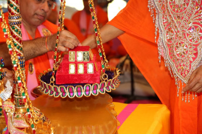 Acharya Swamishree places gold on the scales for the Suvarna Tula