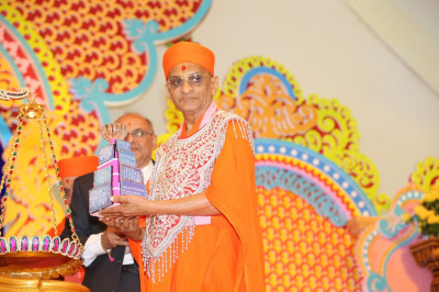 Acharya Swamishree prepares to place the diamond arrangement on the scale