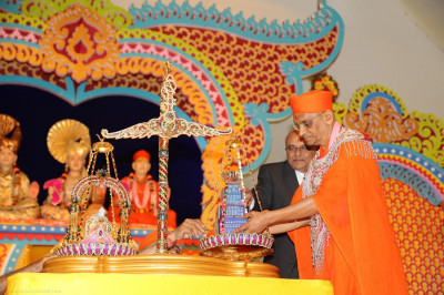 Acharya Swamishree places the diamond arrangement on the scale