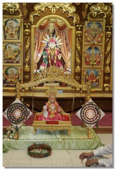 The divine darshan of Jeevanpran Bapashree seated on a golden swing and Lord Shree Swaminarayan
