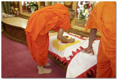 Acharya Swamishree performs a ritual ceremony on the new flags before they go up on the sikhars