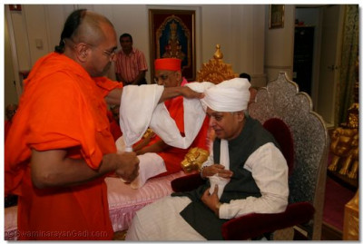 Sadguru Shree Munibhushandasji Swami ties a prasad paag on Mr. Ashok Bhatt