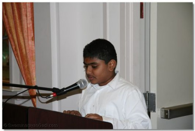 A young disciple reads a piece from the English Vachnamrut to please the Lord