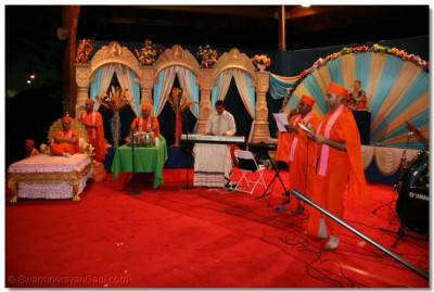 Sants sing kirtans as more sants and disciples play musical instruments for accompaniment