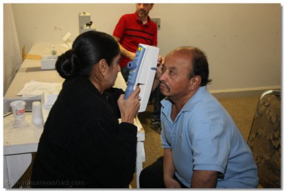 A patient gets his eyes checked by a doctor