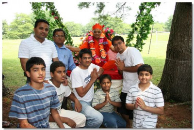 Acharya Swamishree blesses disciples as He is seated on the swing