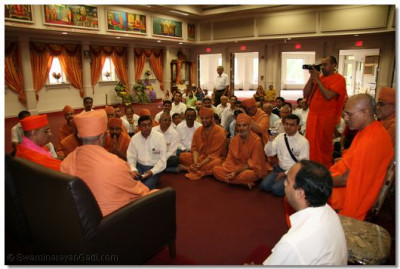 Acharya Swamishree and Swami Hariprasadji sit in front of the congregation