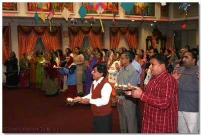 Disciples offer aarti to the Lord