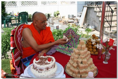 Acharya Swamishree offers cake to Harikrishna Maharaj at a disciple's home in New Jersey