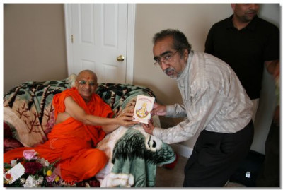 Acharya Swamishree presents a Shikshapatri to a disciple's friend in Connecticuit