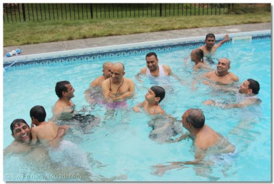 Acharya Swamishree, sants, and disciples go for a swim in a disciple's pool in Connecticuit