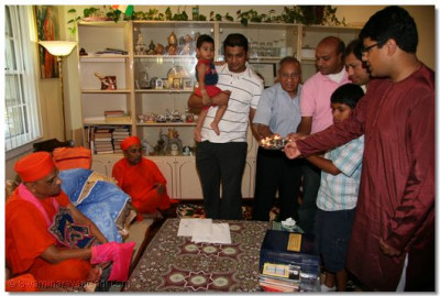 Disciples perform aarti to Acharya Swamishree in their home in New Jersey