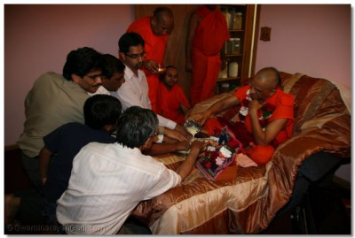 Acharya Swamishree and disciples perform panchamrut snan in a disciple's home in New Jersey