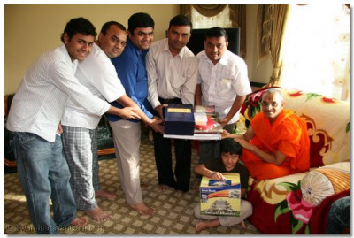 Acharya Swamishree presents disciples with a set of scriptures, which were inaugurated during the Shree Muktajeevan Swamibapa Shatabdi Mahotsav in October 2007