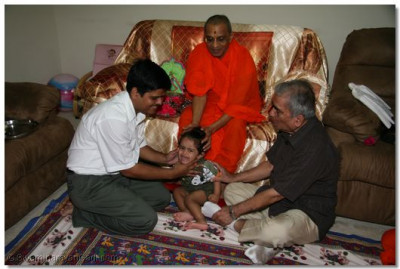 A young child is fortunate to receive Acharya Swamishree's divine blessings