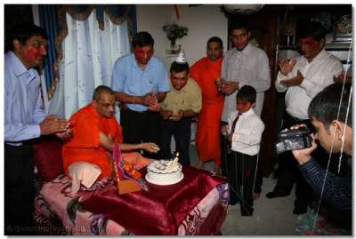 Acharya Swamishree cuts a welcoming cake that the disciples have lovingly offered to Him
