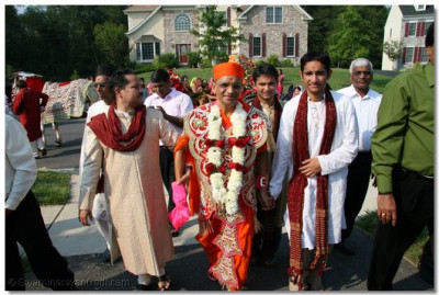 Acharya Swamishree is lead into the disciple's home