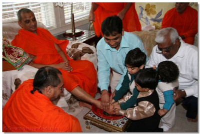 Disciples take the opportunity to bathe Acharya Swamishree's lotus feet