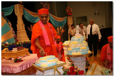 Acharya Swamishree lights the birthday candles on the cakes