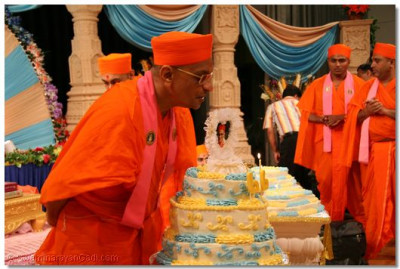 Acharya Swamishree blows out the candles on the cakes