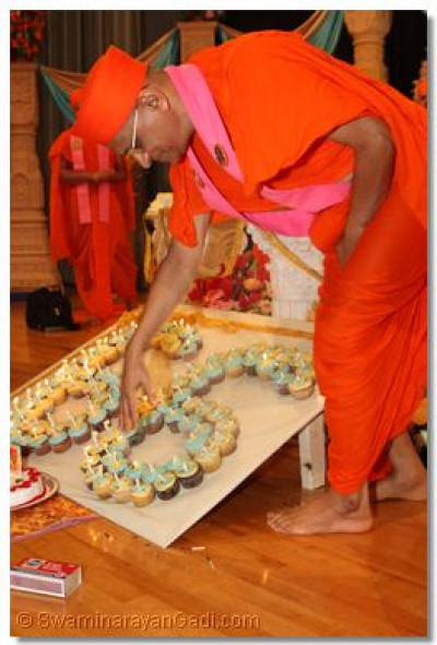 "Acharya Swamishree blows the candles on the large ""66"""