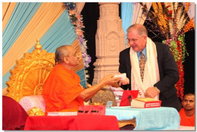 Acharya Swamishree gives prasad to John Reilly