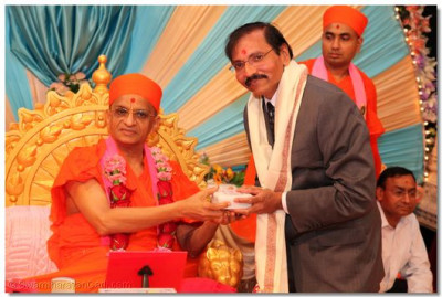 Acharya Swamishree blesses and gives prasad to Dr. Kiritbhai S. Patel