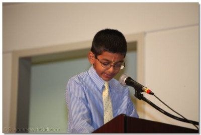 "A young disciple reads a section from ""Ghanshyam Baal Lila"""