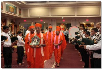 The sants proceed through the aisle whilst carrying the murti of Harikrushna Maharaj