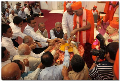 Sants and disciples perform panchamrut snan to the murti of Shree Harikrushna Maharaj