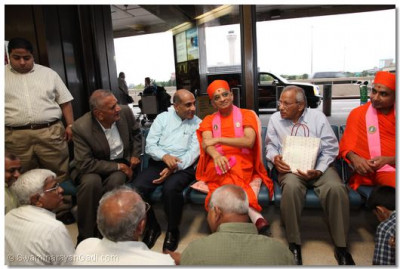 Acharya Swamishree, sants, and disciples sit in the airport waiting area