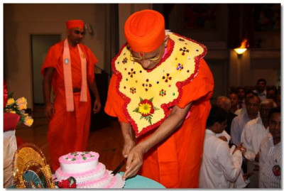 His Divine Holiness Acharya Swamishree cuts a celebration cake in honor of the Gurupoornima celebration