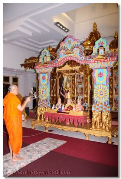 Acharya Swamishree performs aarti to the candy hindola