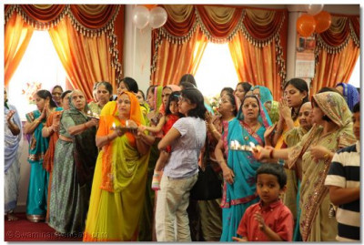 Disciples perform aarti to the Lord