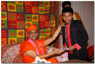 Acharya Swamishree presents a disciple with an award for his speech