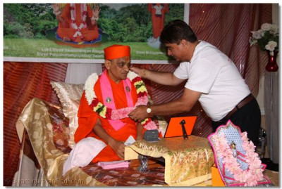 A disciple places a flower garland on Acharya Swamishree