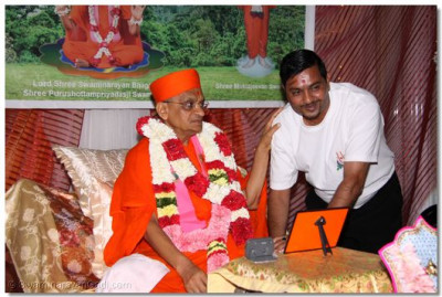 Another disciple places a flower garland on Acharya Swamishree