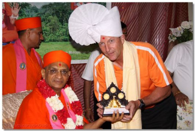 Acharya Swamishree presents an award to a member of the community