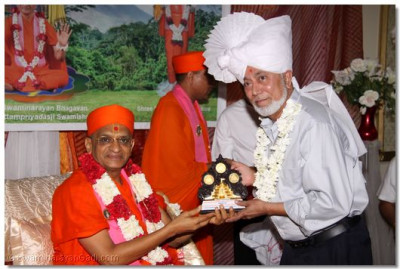 Acharya Swamishree presents an award to another member of the community