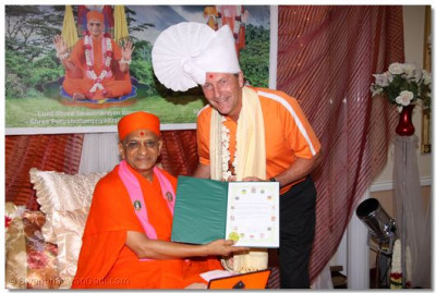 A member of the local community presents Acharya Swamishree with an award
